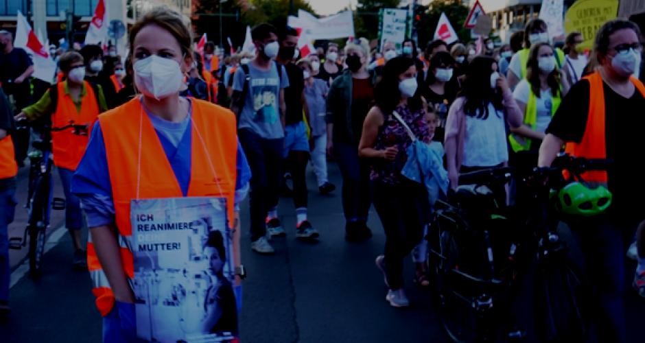 """Demonstration von Krankenhausarbeiter_innen, eine Pflegerin im Vordergrund trägt ein Schild mit der Aufschrift: """"Ich reanimiere deine Mutter"""""""