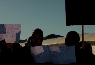 Sechs Frauen in einer Wüstenlandschaft halten Protestschilder hoch